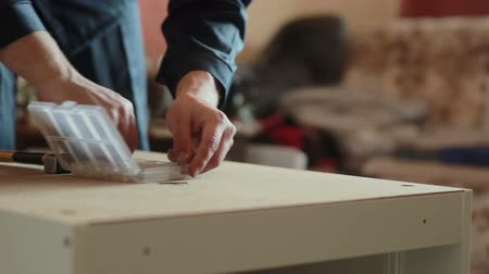 isabet : man assembles parts of furniture using a hammer. Stok Video