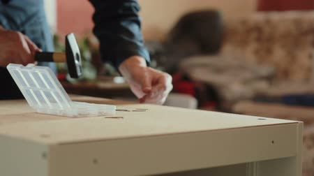 мебель : man assembles parts of furniture using a hammer. Стоковые видеозаписи