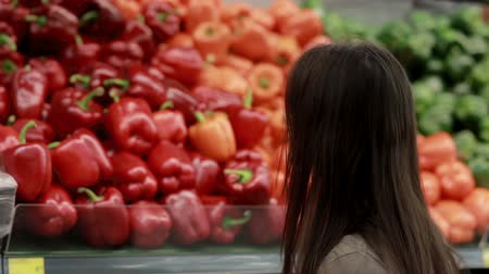 recados : Young woman chooses paprika on store shelves.