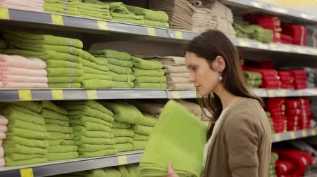 gondol : Young woman chooses towels in the supermarket Stock mozgókép