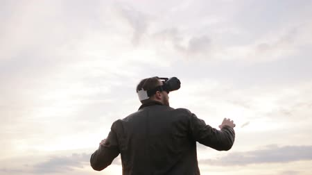 realidade : man uses a virtual reality glasses against the sky