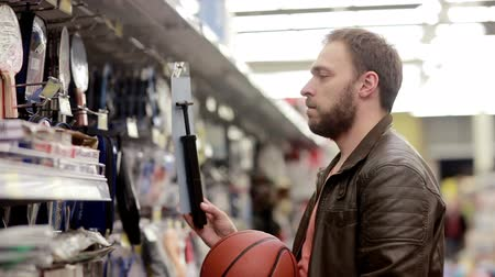 aisles : Man chooses sporting goods in store