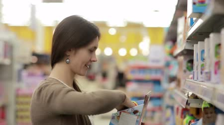 купить : Young woman chooses baby toys in the supermarket