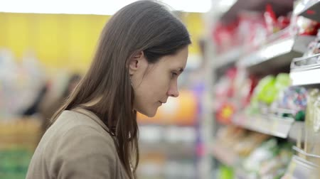 aisles : Girl selects the item on the shelves in the store