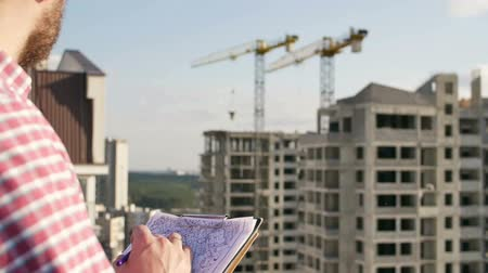projects : engineer looking on project on construction site Stock Footage