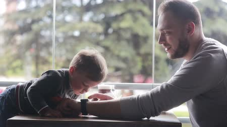 paternal : little boy looks at smartclock on fathers hand