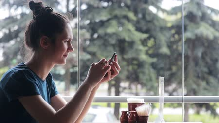 cellphone : Woman using smartphone sitting near the window Stock Footage