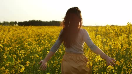 walking back : girl runs arms outstretched through a field slowmo Stock Footage