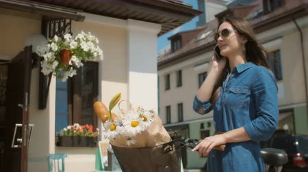 hipster : Beautiful brunette smiling girl wearing sunglasses standing near cute building with bike talking on phone. 4K Stock Footage