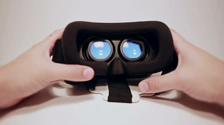 fejhallgató : Mans hands take virtual reality glasses for smartphone and wear them, smartphone is working, white background