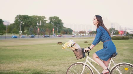 bicycle : Side view of a brunette girl with long hair riding a bike in the city with flowers in a basket, slow mo, steadicam shot Stock Footage