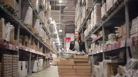 работник физического труда : A young brunette woman pushing a trolley with lots of boxes between shelves with goods in a warehouse