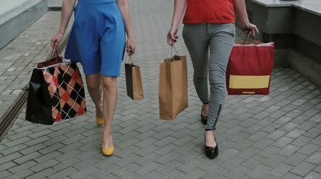 покупка товаров : legs slender young girls walking down the street past the store with shopping bags, slow mo stedicam shot