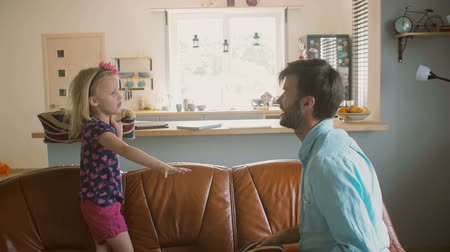 couro : A young father and his cute happy little daughter having pillow fight on the sofa. Slow motion, Steadicam shot