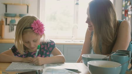 kitchen paper : Mother is smiling while talking to her little daughter who is colouring a picture on the kitchen table. Slow mo