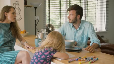 kitchen paper : A husband working on his tablet and talking to his beautiful wife at the kitchen table. Slow mo Stock Footage