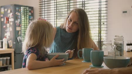 cereais : Beautiful young mother is talking to her cute blond daughter at breakfast and smiling. Slow mo Vídeos