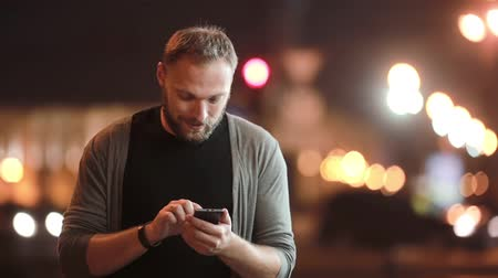telefone celular : Handsome man walks, smiles, uses his smartphone and goes away. Blurred city lights in the street. Modern technology. Stock Footage