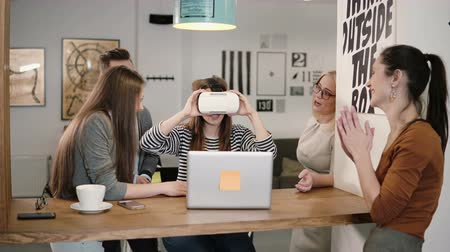 нововведение : girl takes off her glasses virtual reality after using the new app share experiences with team in the startup office.