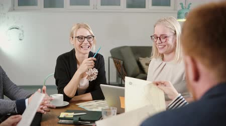 discussion meeting : Creative business team at the table in startup office happy beautiful blonde women are involved in the conversation Stock Footage