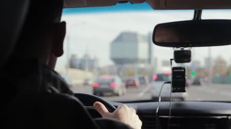 zadní : Backview of a man driving a car in a city. Blurred sights. Big interesting building in the distance. Traveling by car.