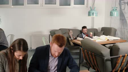 avoiding : young man is resting avoiding the work sitting on sofa uses smartphone and eating apple while his colleagues are working Stock Footage