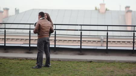 kapcsolatok : Young couple have fun, laugh standing on a roof. A beautiful view of brunette lovers. Happy love relationship. Stock mozgókép