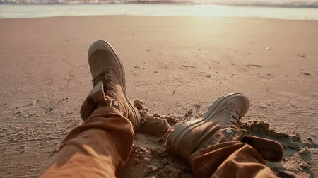 estância turística : A view of a beautiful pastel sunset at the shore with a close up of two boots resting on the beach. Stock Footage