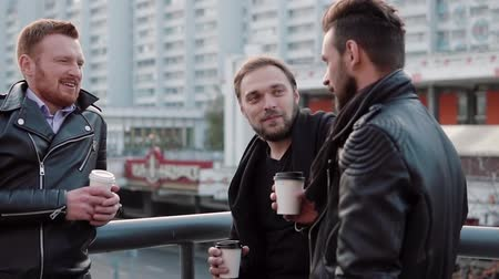 дружба : Three handsome young men with beards talk, smile and have coffee on the go near a bridge railing in the city. Slow mo Стоковые видеозаписи