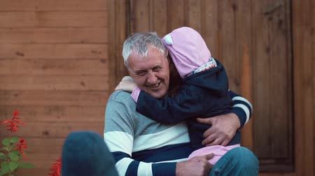 relação : An ageing man is having great time with his grandchildren. He hugs them, they run into his embrace. Slow mo Stock Footage