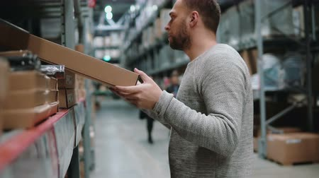 munkás : Young man taking a pasteboard box from a shelf, holds in hands item in a warehouse. 4K Stock mozgókép