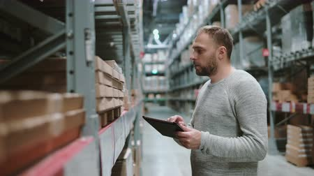 elosztó : Young man using digital tablet in warehouse, checking goods list to buy right at supermarket and looking for items. 4K Stock mozgókép