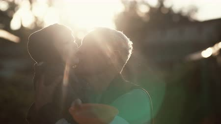 grandchild : CLose-up of grandfather holding grandson on hands, hugs and kiss boy on cheek. Old man standing outdoor in sunlight. 4K Stock Footage