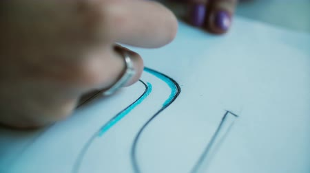 escrever : Close-up view of woman s hand coloring layout of shoes with blue pencil. Young designer developing new collection. 4K Vídeos