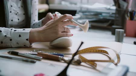 дизайнер : Woman sitting at the table with tools and making measurements of wooden last.After that picks up heel for shoe. 4K