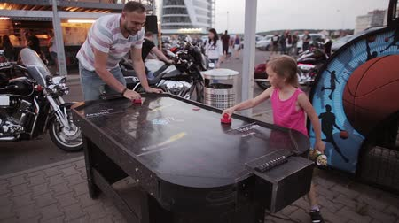 stay active : Father and daughter spending time together on a playground. Little girl and man playing air hockey. Stock Footage