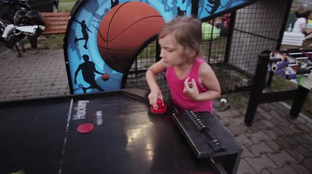 stay active : Close-up view of happy little girl playing air hockey with father. Competition between dad and daughter on a playground.