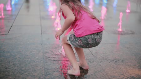 temporadas : Cute little girl playing with colored water jets at the fountain in hot summer day.