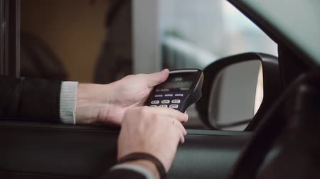 chip and pin : Man paying credit card for buying inside car, enters a PIN code. Close-up view of businessman hand from the car window.