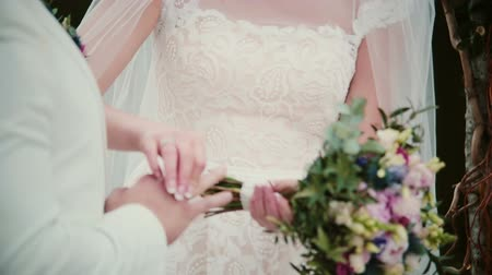 colocando : On a wedding day bride puts a golden ring on a groom finger. Close-up exchanging wedding rings.