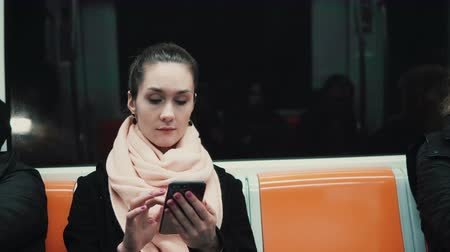 общественный : Attractive girl in subway train using smartphone. Young woman browse the Internet with touchscreen technology.