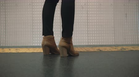platforma : Close-up view of woman foot wearing shoes in subway platform. Girl standing near restrictive line and waiting train.