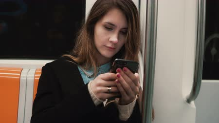 Portrait of attractive girl in subway train using smartphone. Young woman chatting with friends and smiling. Stock Footage