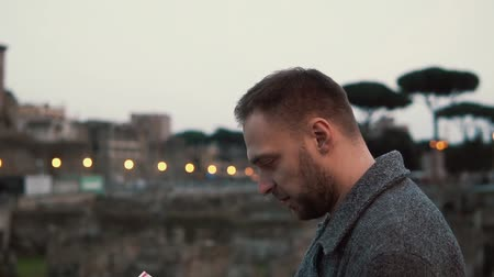 борода : Handsome brunette man with a beard standing at the ruins in Rome, Italy, looking at map in his hands. Slow motion. Стоковые видеозаписи