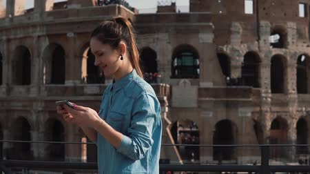 A young tourist woman takes selfie photo at the Colosseum in Rome, Italy with smartphone smiling, laughing. Slow motion.