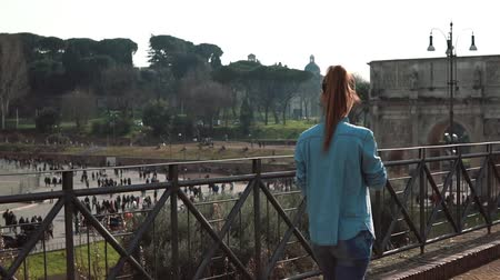 arch of constantine : Woman walks down the street in Rome, Italy, takes photos of Colosseum, arch of Constantine with smartphone. Slow motion.
