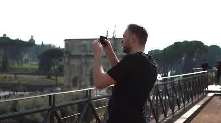 arch of constantine : Man tourist takes photos of landscapes in Rome, Italy on smartphone. The Konstantin s arch on background. Slow motion.