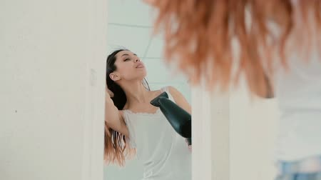 dryer : Young woman standing in front of mirror in pajamas. Girl using hair dryer and sing, wind blowing the hair. Slow motion.