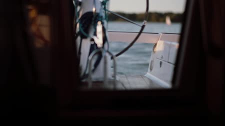 námořník : View inside a cabin of the ship. The captain driving the yacht standing behind a wheel in the open water.