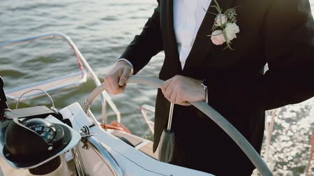námořník : Close-up view of the groom in a wedding suit standing behind steering wheel on the yacht. Man driving the ship in sea.